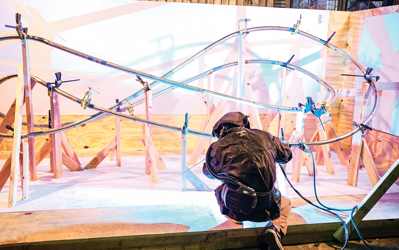 Photograph of a student welding the sculpture