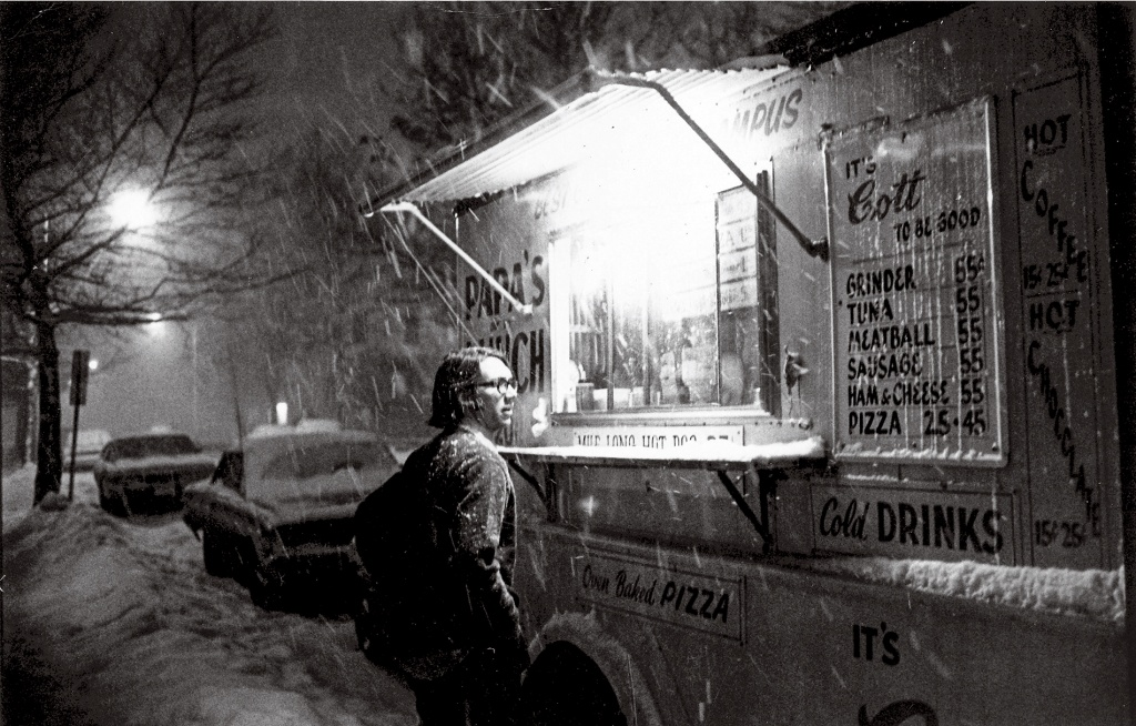 Archive photo of a student standing in front of a food truck in the snow.