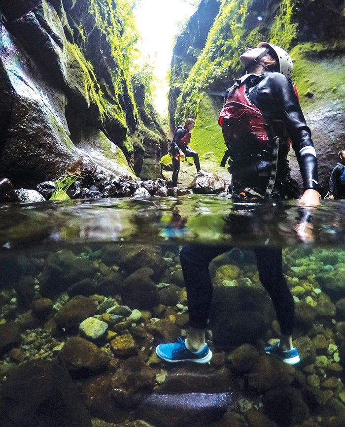 Photograph of a man standing in a river in a canyon, dressed in outdoor gear.