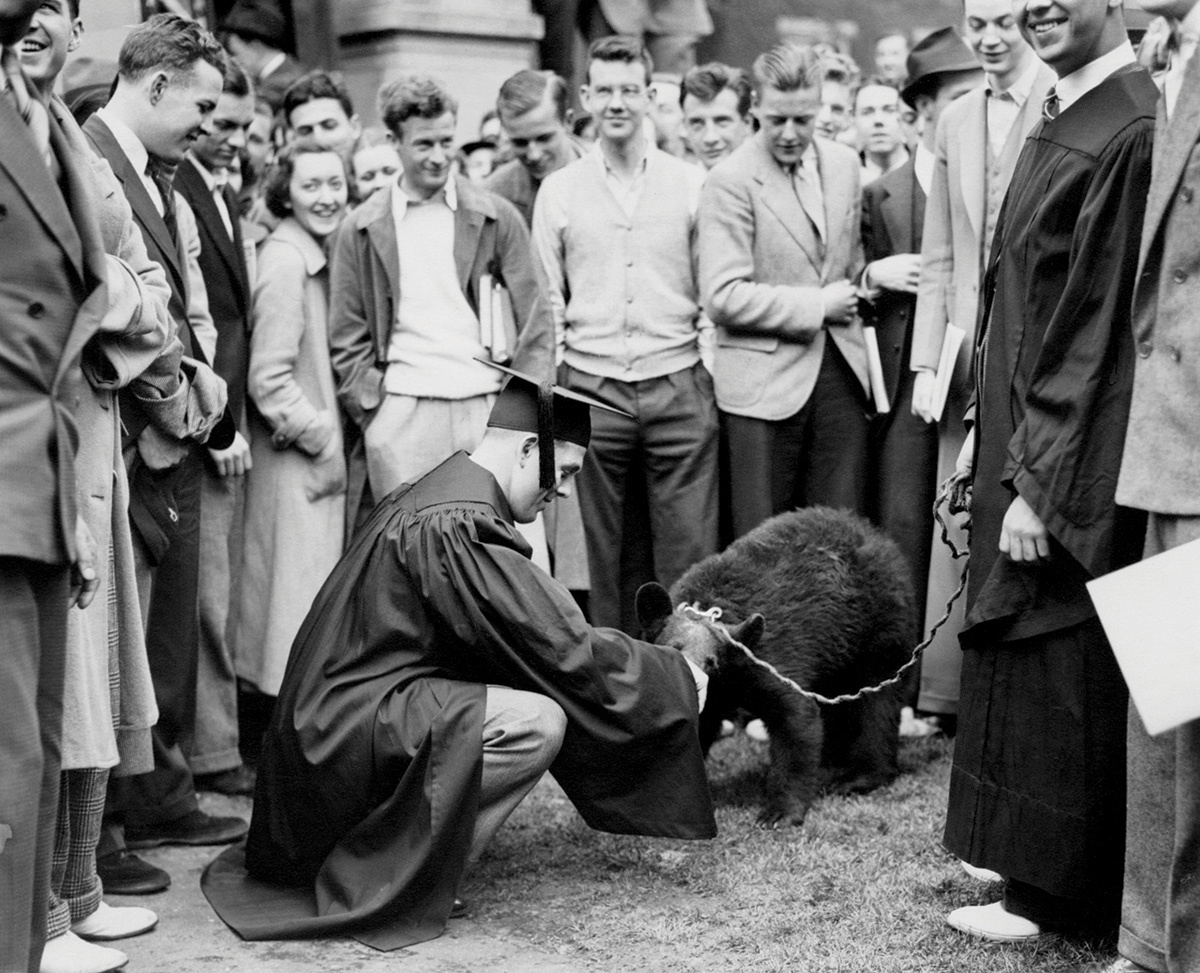 Vintage photograph of a bear being petted by a man in a cap and gown, surrounded closely by a group of people.