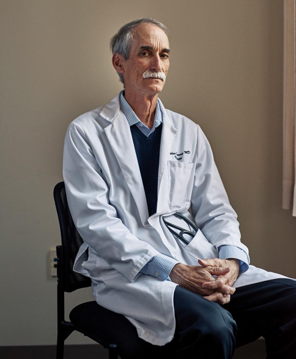 Photograph of Professor Stephen Salloway sitting, wearing a lab coat.