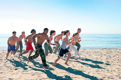 Photo of a group of people running on the beach.
