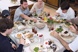 Photo of a group of students crowded around a table for a meal.