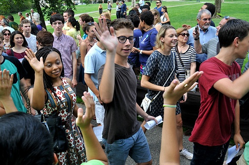 Photo of students walking and high fiving.