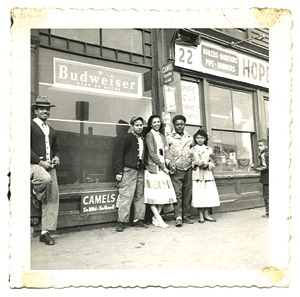 Vintage photo of five people standing against a storefront.