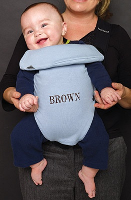 """Photo of a baby in a carrier that is embroidered """"BROWN""""."""