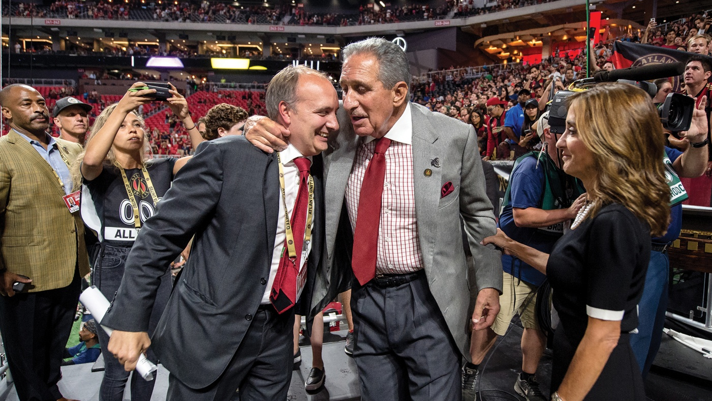 Photograph of Darren Eales '95 hugging Falcons and Atlanta United owner Arthur Blank in a stadium