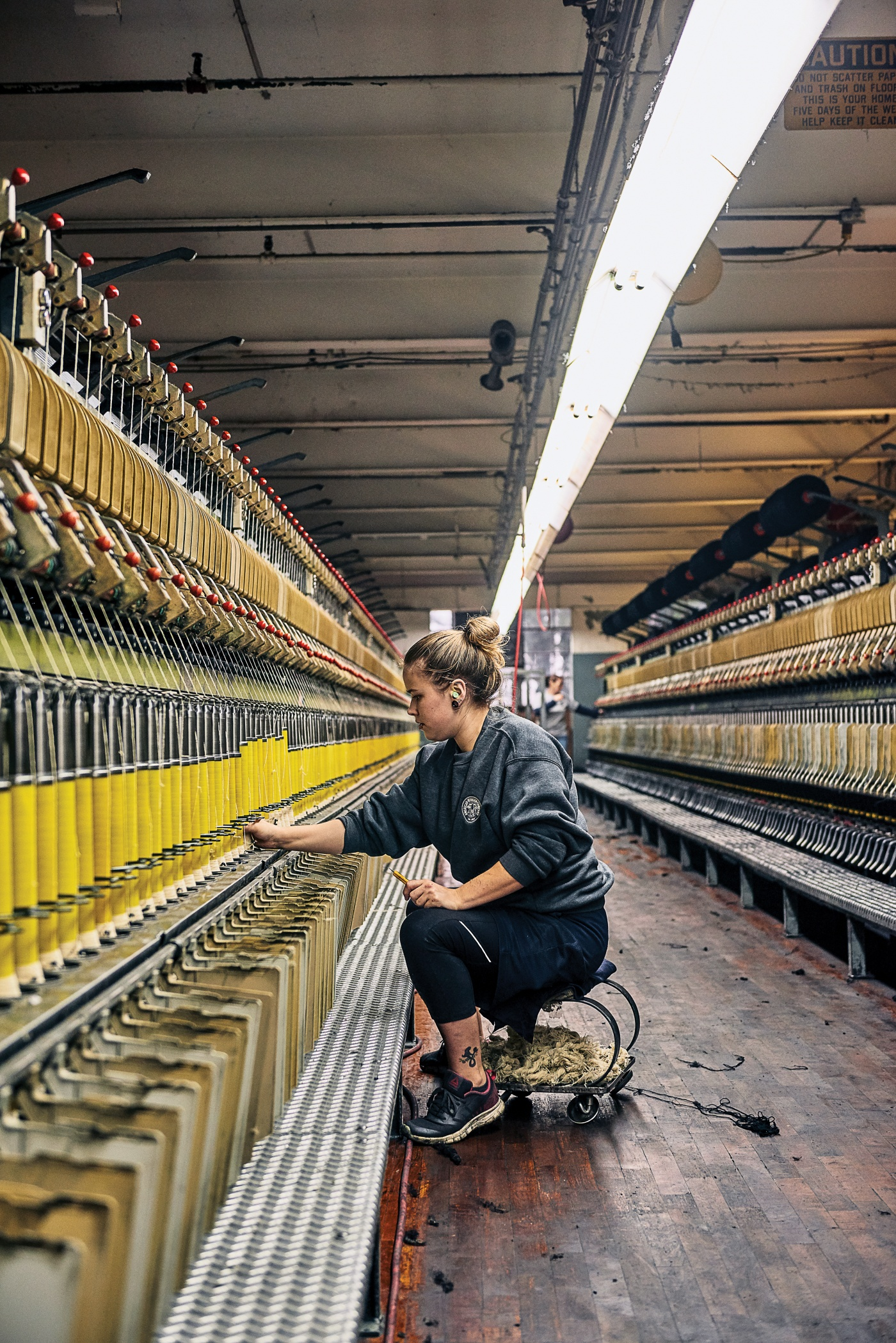 An American Woolen staffer tends to a woolen spinning frame