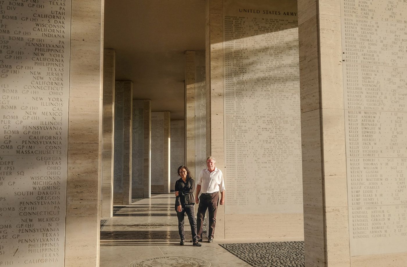 Mark Gillen '77 and his wife, Delmafe Festin, standing at the Manila American Cemetery between stone columns