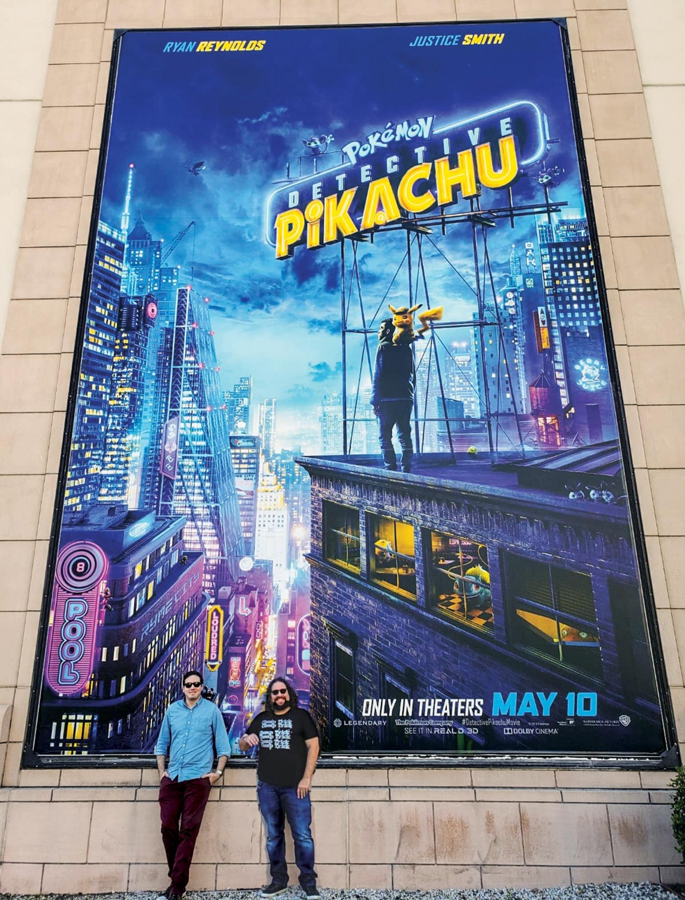 Dan Hernandez '06 and Benji Samit '06 standing in front of a Pokémon: Detective Pikachu poster