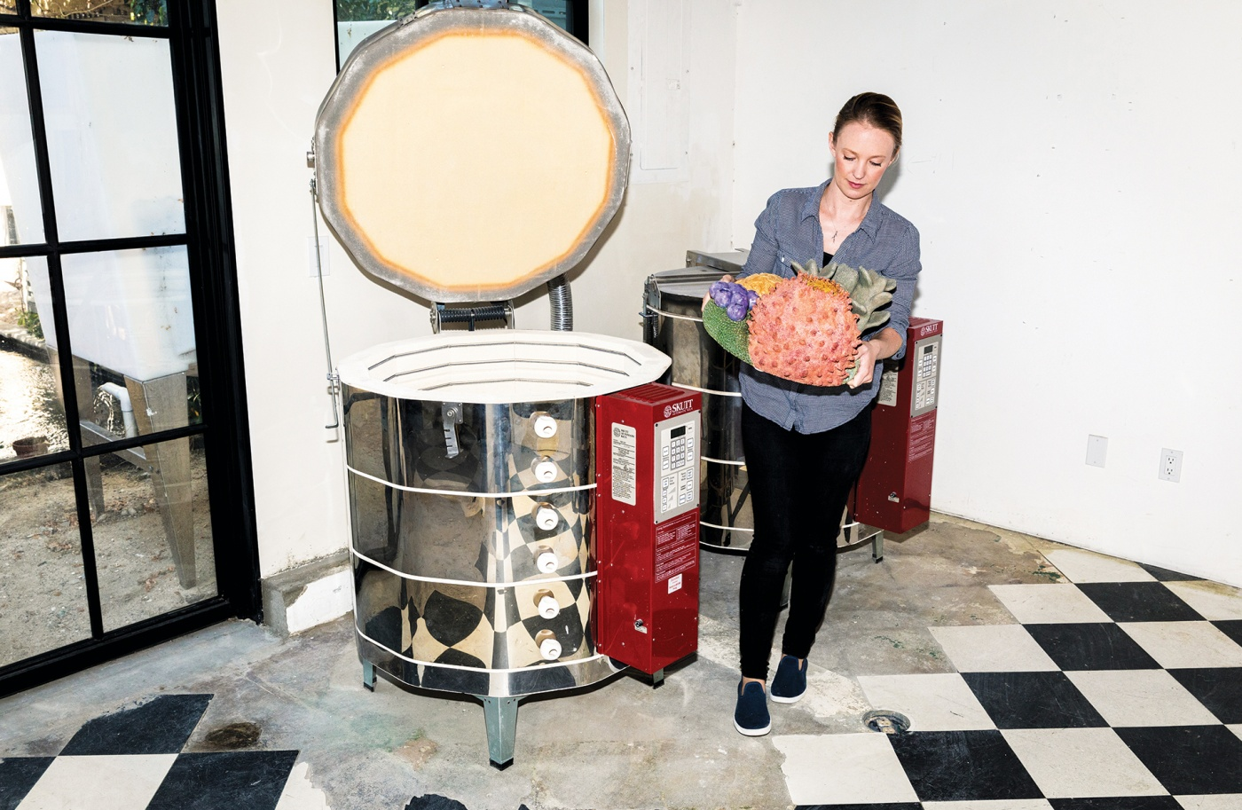 Courtney Mattisson removes a ceramic piece from the kiln in her studio
