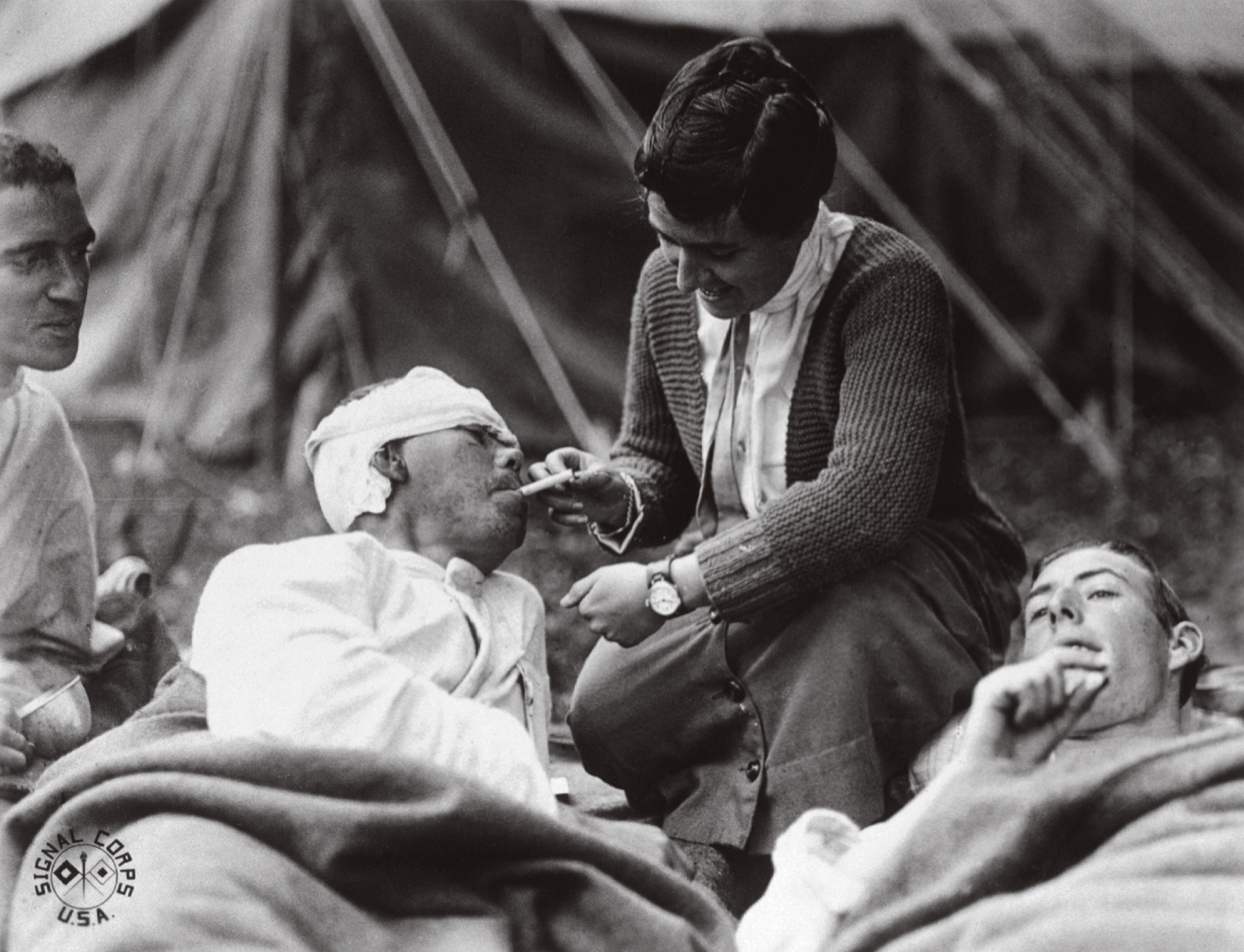 A WWI nurse administers to wounded soldiers