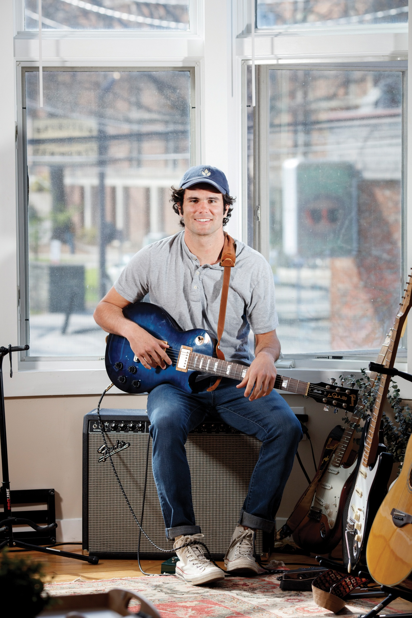 Aidan Reilly playing guitar in his dorm room.