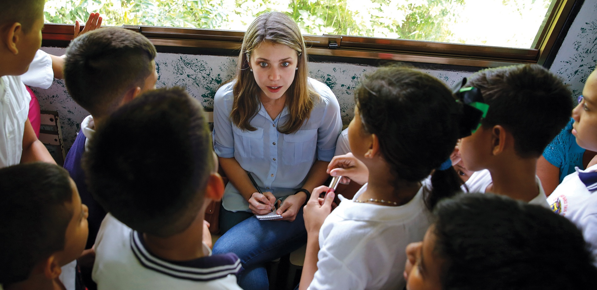 Image of Alexandra Ulmer taking notes, surrounded by Venezuelan children.