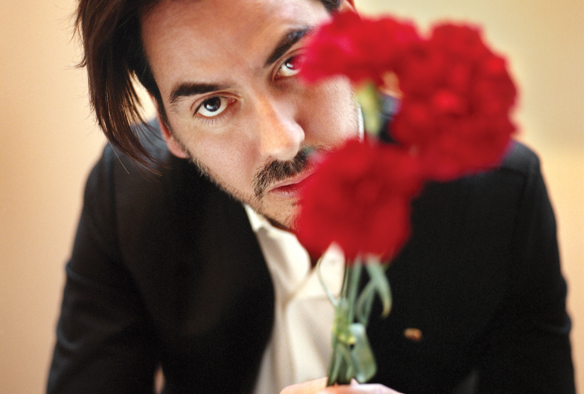 Image of Dhani Harrison '01 in a black suit and white shirt, face partially obscured behind bright red flowers.