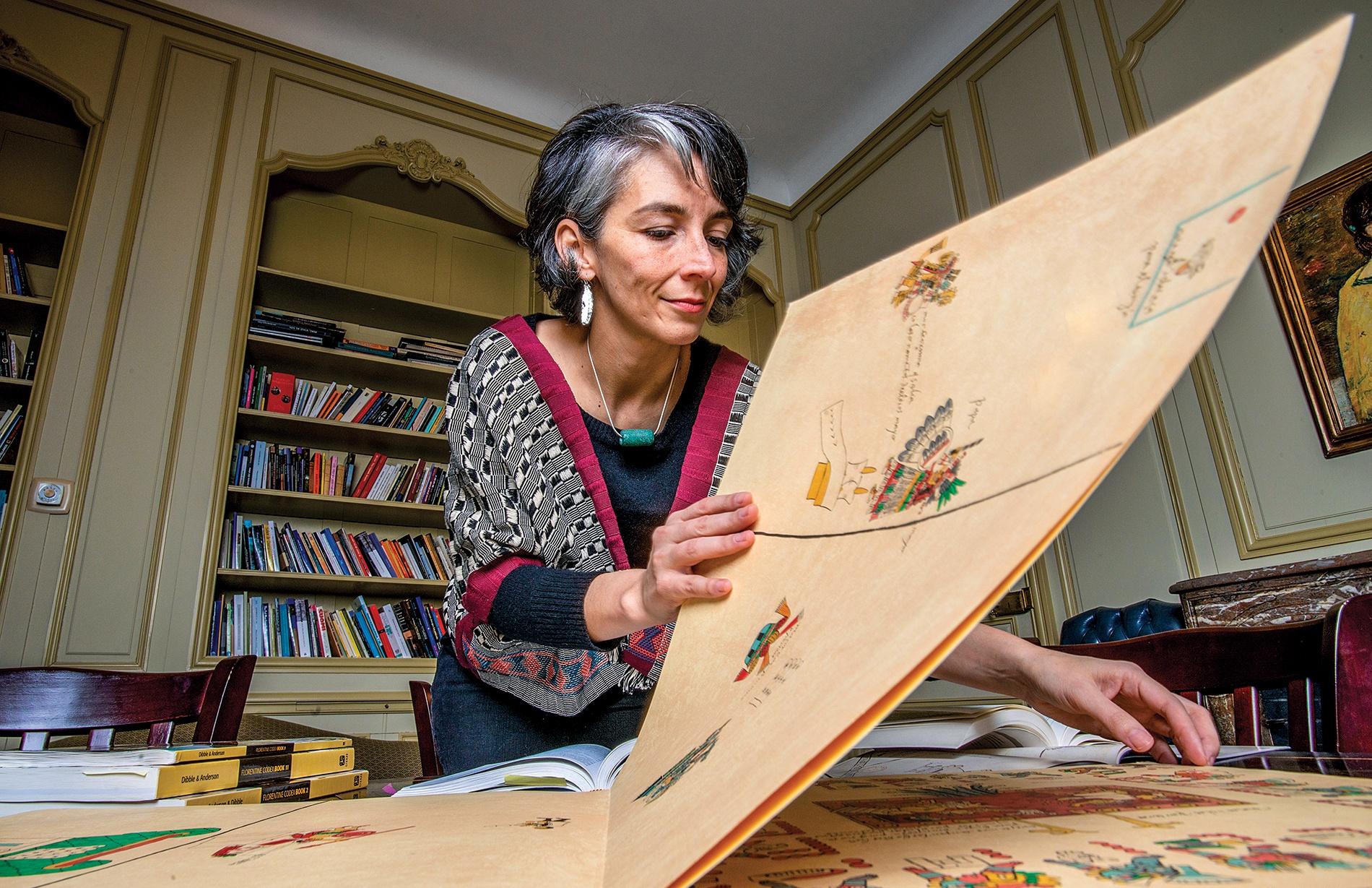 Prof Iris Montero leafing through a folio