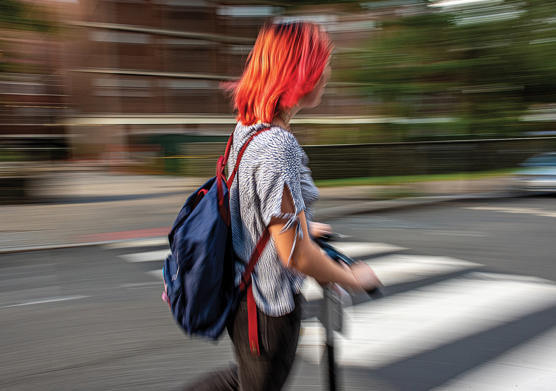 Motion-blurred photo of a student on a scooter
