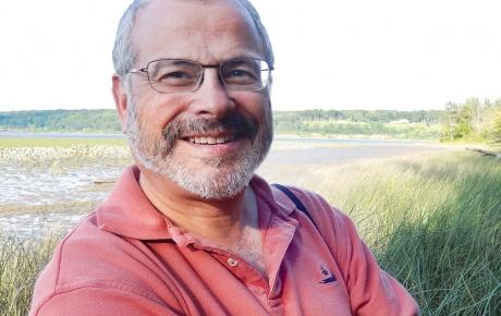 Photo of Joel Scheraga, with wetlands in the background.