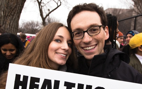 "Photo of Kira Ganga Kieffer '08 and Aaron Eisman '08, at a rally with a sign that says ""Healthcare is a Human Right."""