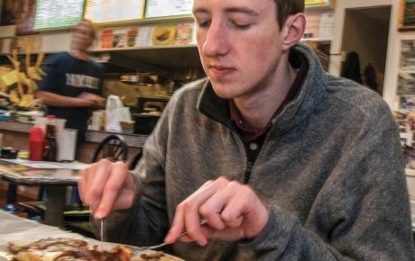 Student Peter Deegan eats pancakes at Louie's