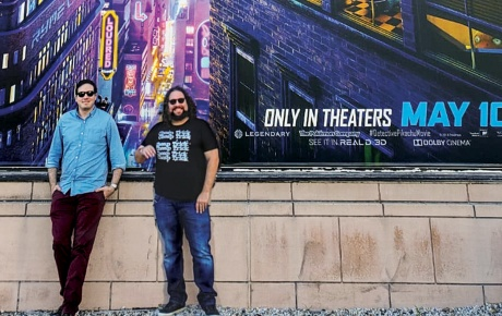 Dan Hernandez '06 and Benji Samit '06 standing in front of a Pokémon: Detective Pikachu poster