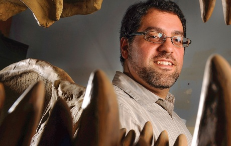 Matthew Carrano '91 grins alongside some dinosaur teeth