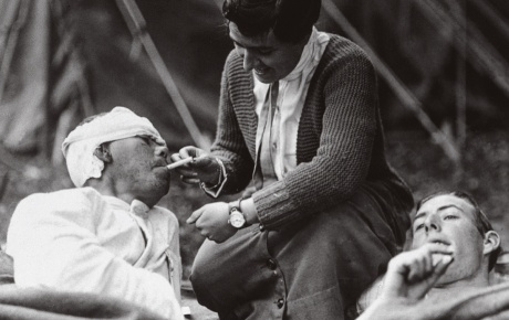 A WWI nurse lights the cigarette of a wounded soldier